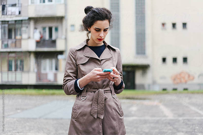 Brunette woman holding her smart phone outdoor by Marija Kovac for Stocksy United