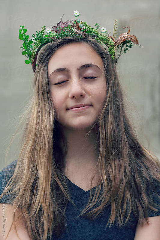 Teen girl with long hair and her eyes closed - homemade wreath of leaves and flowers on her head by Carolyn Lagattuta for Stocksy United