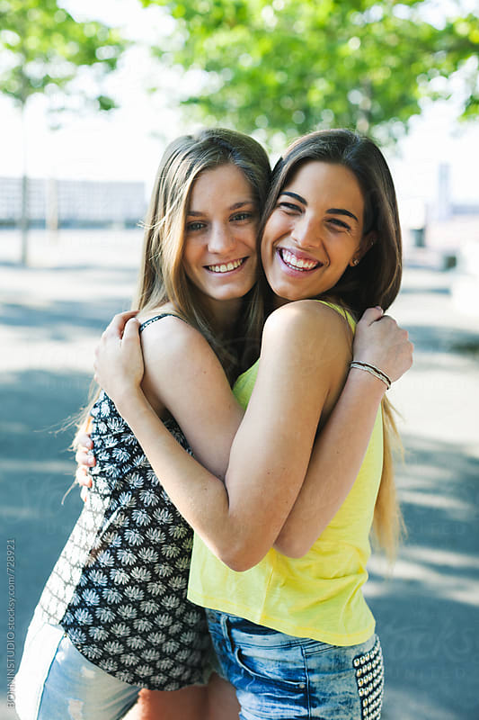 Young female friends embracing together standing in a park. by BONNINSTUDIO for Stocksy United