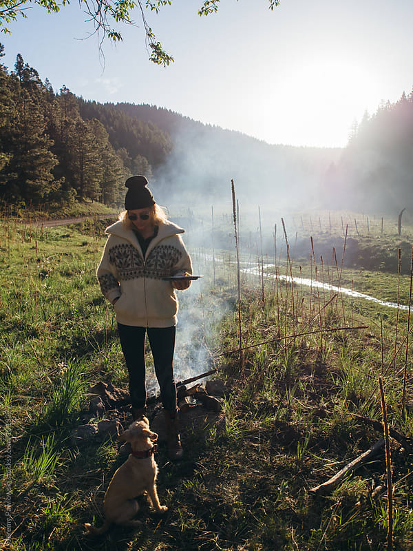 Dog looking at woman in jacket while camping by Jeremy Pawlowski for Stocksy United