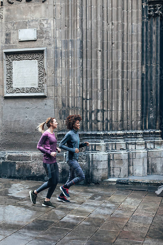 Two young multiethnic women running on Barcelona streets.  by BONNINSTUDIO for Stocksy United