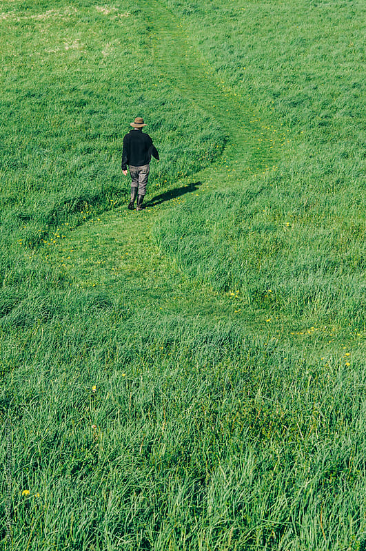 Man walking on a path winding through a lush field by Deirdre Malfatto for Stocksy United