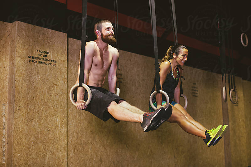 Couple training with rings in a gym box. by BONNINSTUDIO for Stocksy United