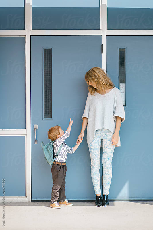 Mother and son holding hands in front of a school by Ania Boniecka for Stocksy United