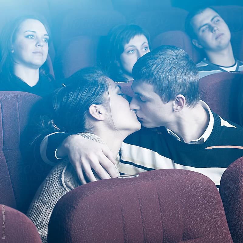 Young couple kissing in movie theater. by Ilya for Stocksy United