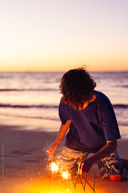 Boy playing with sparklers at the beach at night by Angela Lumsden for Stocksy United