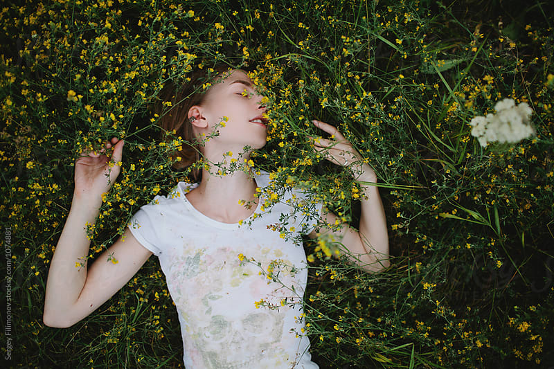 Beautiful blonde girl lie down in yellow flowers by Sergey Filimonov for Stocksy United