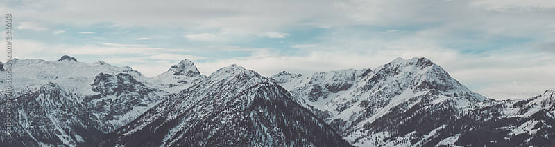panorama shot of snowcovered mountain peaks by Leander Nardin for Stocksy United