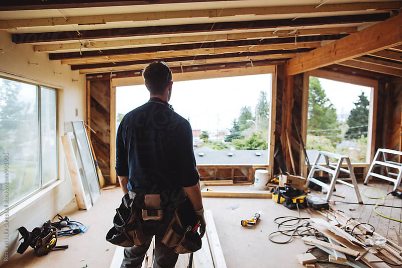 Carpenter looking at renovation jobsite by Rob and Julia Campbell for Stocksy United