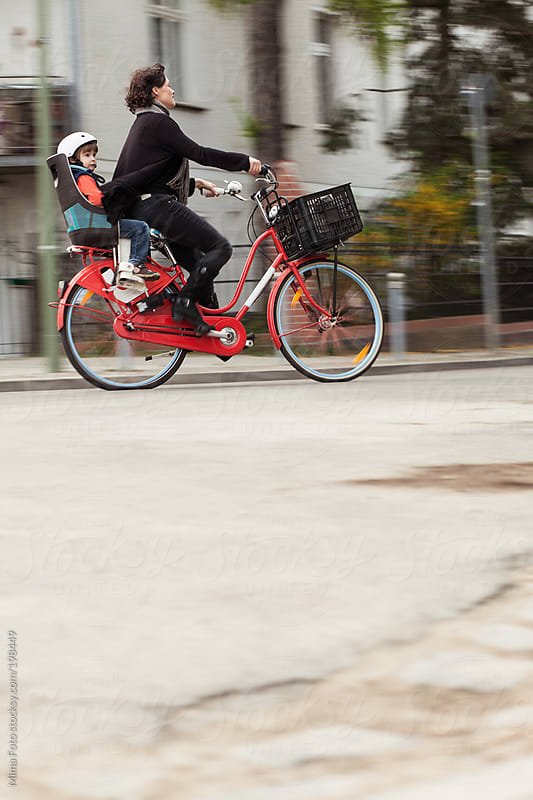 Mother and son riding on bike by Mima Foto for Stocksy United