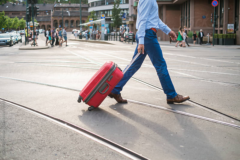 Elegant man with the suitcase is crossing the tram rails by Jelena Jojic Tomic for Stocksy United