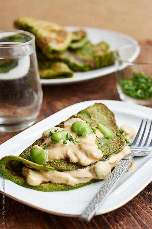 Spinach pancakes with fava beans by Harald Walker for Stocksy United