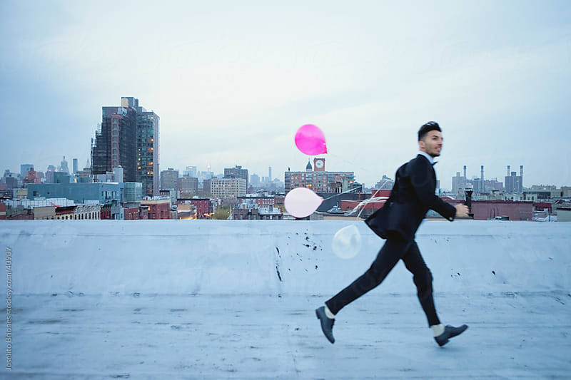 Excited Young Man Running with Balloons on Rooftop in New York by Joselito Briones for Stocksy United