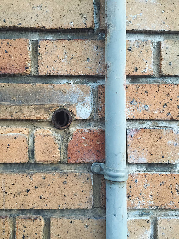 Close up of brick wall and utility pipe by Paul Edmondson for Stocksy United