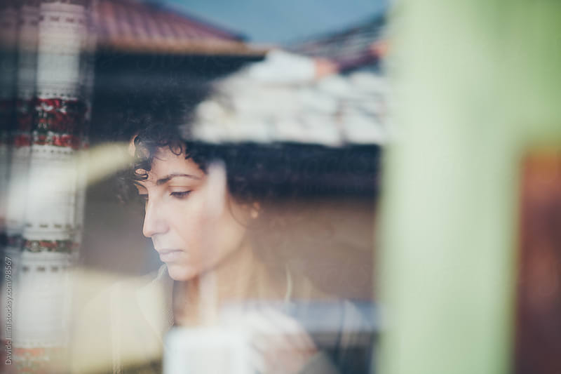 Young worried woman at the window by Davide Illini for Stocksy United