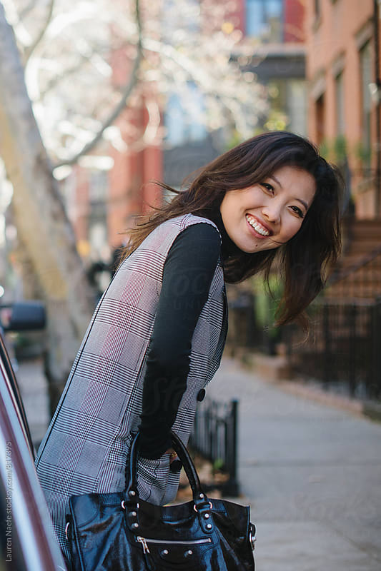 Young woman leaning against car and smiling by Lauren Naefe for Stocksy United
