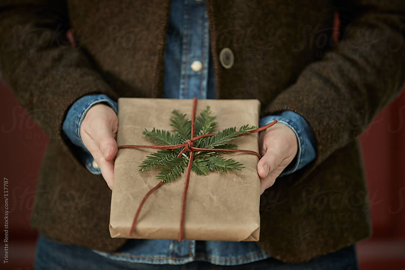 Woman holding homemade wrapped gift  by Trinette Reed for Stocksy United