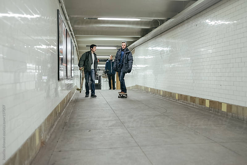 Young Male Student Friends Navigating New York Subway Station Tunnel Walkway with Skateboard by Joselito Briones for Stocksy United