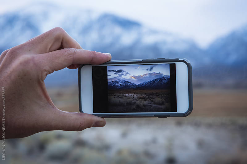 Smart Phone and Snow Mountains by MEGHAN PINSONNEAULT for Stocksy United