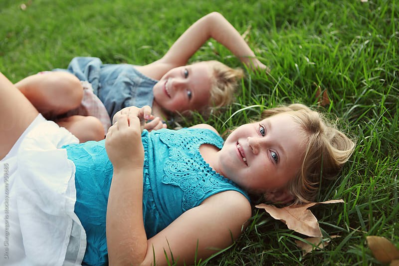 Sisters Laying In Grass Laughing by Dina Giangregorio for Stocksy United