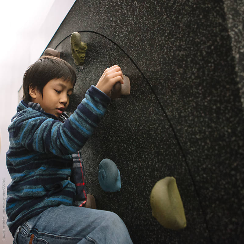 Young kid exploring and playing on the rock climbing wall inside a science exhibit by Lawrence del Mundo for Stocksy United