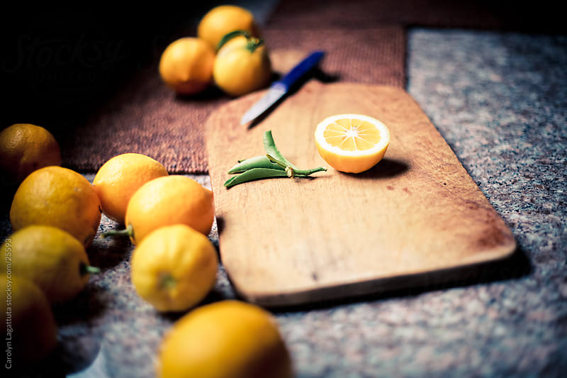 Slicing lemons for homemade lemonade in the kitchen on a wood cutting board by Carolyn Lagattuta for Stocksy United