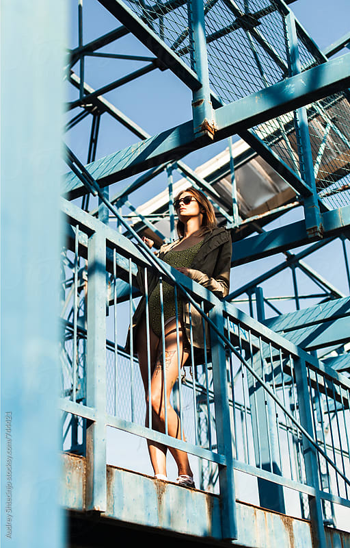 Sensual hip female standing on platform with metal construction in background. by Marko Milanovic for Stocksy United