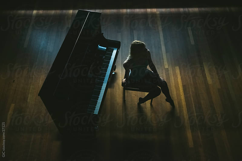 Dancer sitting on a seat in front a piano by GIC for Stocksy United