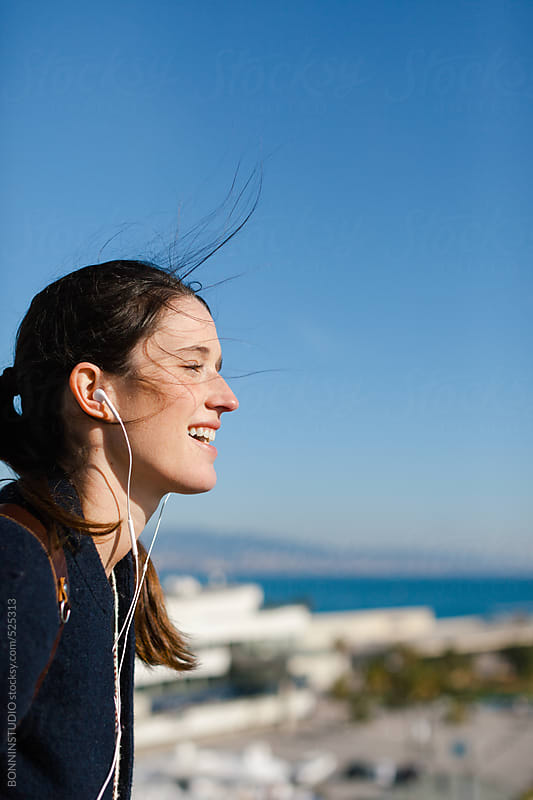 Young caucasian woman enjoying a sunny day whilst listening music with headphones.. by BONNINSTUDIO for Stocksy United