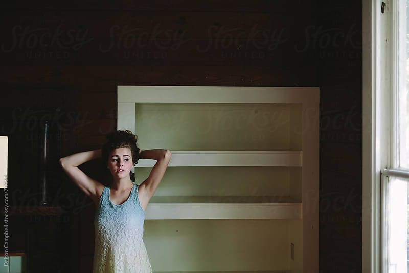 Young girl sitting in empty house in thought by Dalton Campbell for Stocksy United