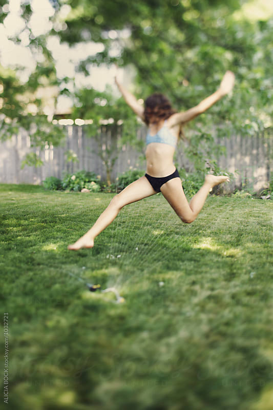 A Teenage Girl Leaping Through A Sprinkler On A Hot Summer Day by ALICIA BOCK for Stocksy United