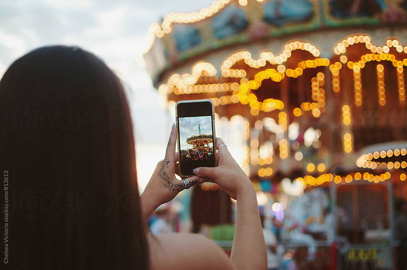 A young woman taking pictures on her phone at a carnival by Chelsea Victoria for Stocksy United