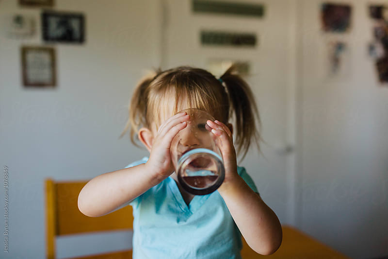 Cute toddler girl drinking from an oversized water glass. by Jessica Byrum for Stocksy United