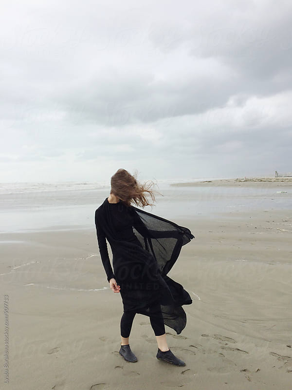Young woman at windy autumn beach by Lyuba Burakova for Stocksy United