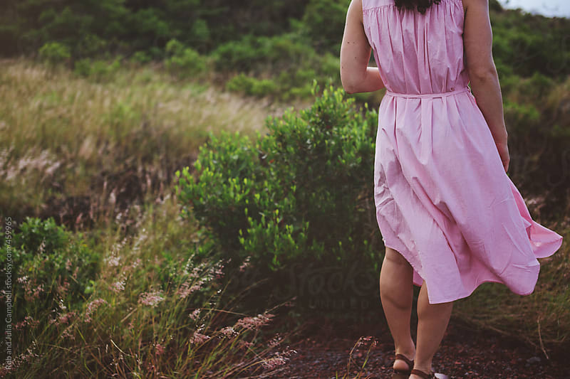 Woman in pink dress with curly brown hair standing in wind outside in nature by Rob and Julia Campbell for Stocksy United