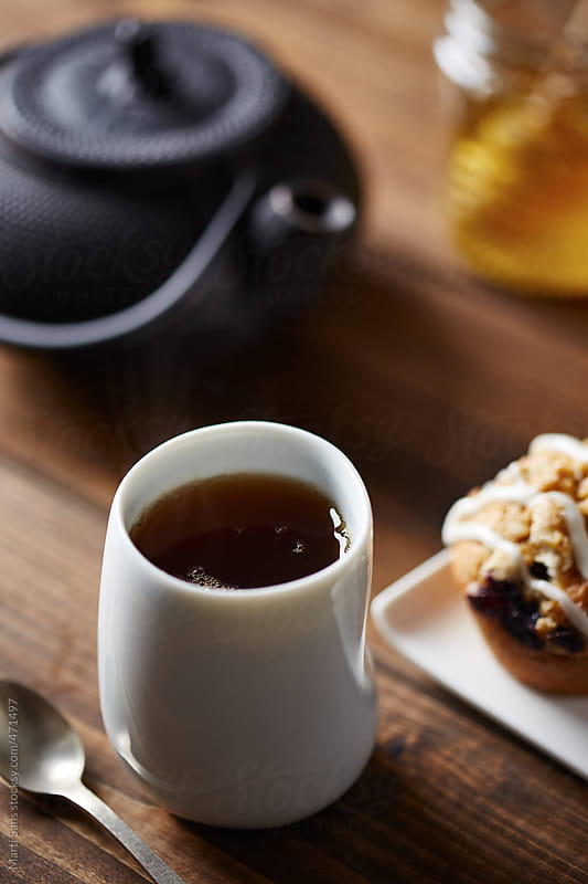 White tea cup and blueberry muffin by Martí Sans for Stocksy United