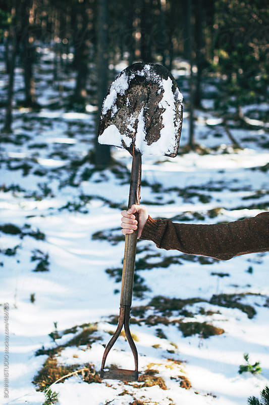 Lumberjack holding an old shovel in a snowy forest.  by BONNINSTUDIO for Stocksy United