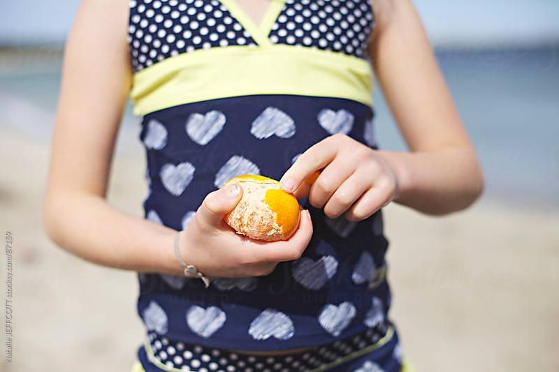 young girl peeling a mandarin by Natalie JEFFCOTT for Stocksy United