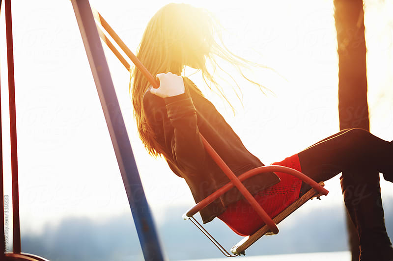 Young woman on a swing by Ilya for Stocksy United