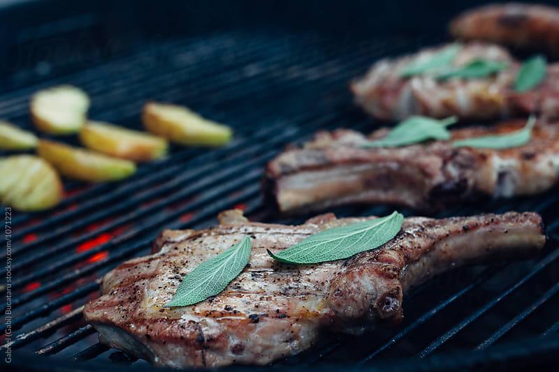 Pork chops on the grill by Gabriel (Gabi) Bucataru for Stocksy United