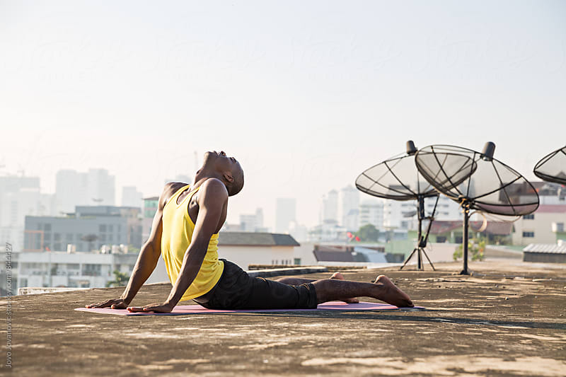 Fit young man in a cobra yoga pose on a city rooftop  by Jovo Jovanovic for Stocksy United