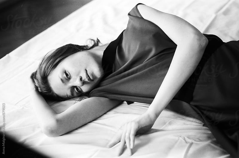 A black and white film portrait of a young woman lying on the bed by Anna Malgina for Stocksy United