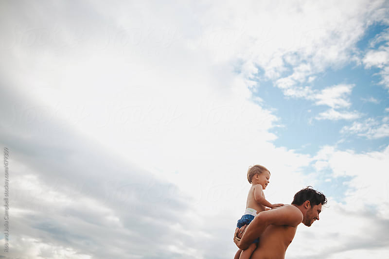 Young dad having fun with toddler son on tropical beach - shoulder ride by Rob and Julia Campbell for Stocksy United