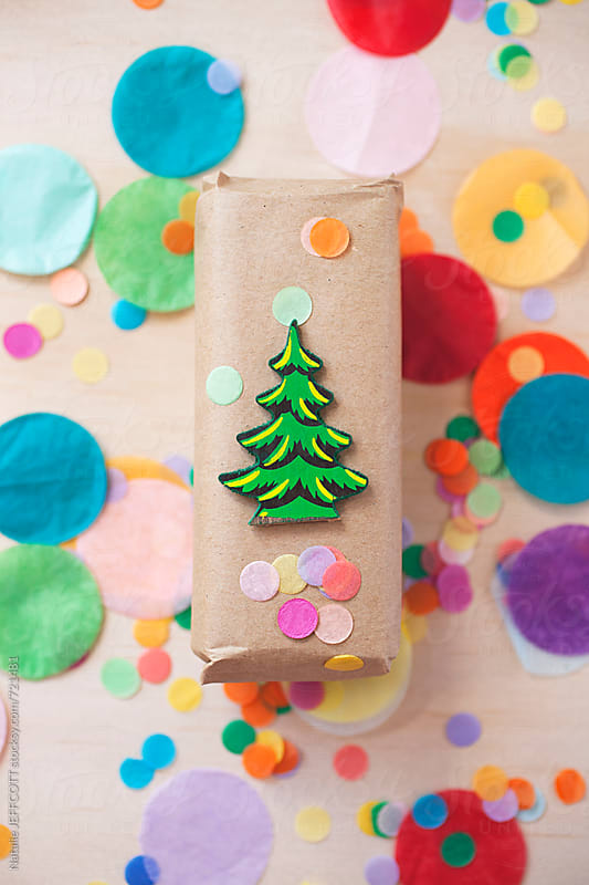 bright and colourful Christmas present with tree ornament and confetti by Natalie JEFFCOTT for Stocksy United
