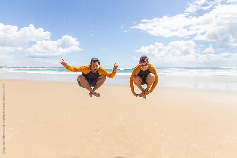 Two young men friends jumping - levitating on an exotic beach in summer by Alejandro Moreno de Carlos for Stocksy United