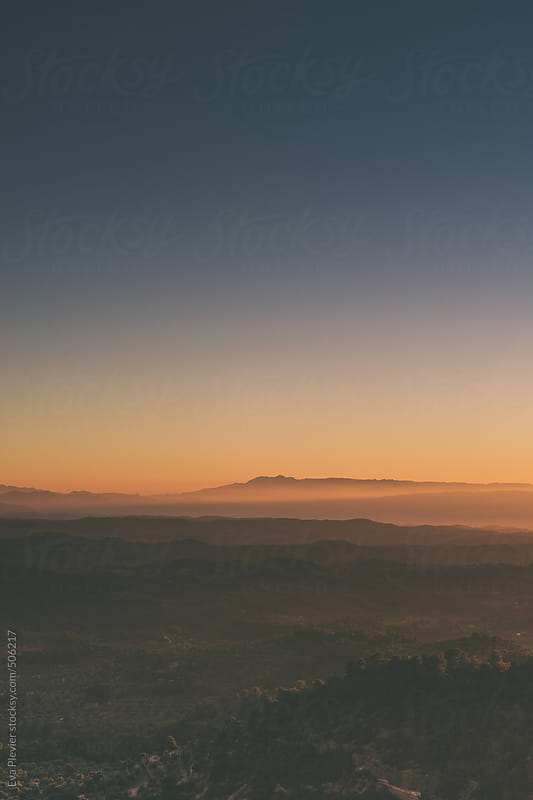 Landscape of foggy hills at sunset. by Eva Plevier for Stocksy United