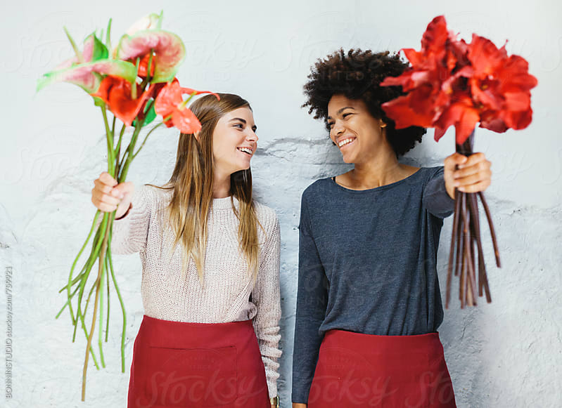 Smiling women holding a bouquet of flowers on a white wall. by BONNINSTUDIO for Stocksy United