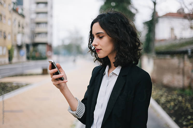 Beautiful brunette woman in suit browsing in her mobile phone in the street by Marija Mandic for Stocksy United