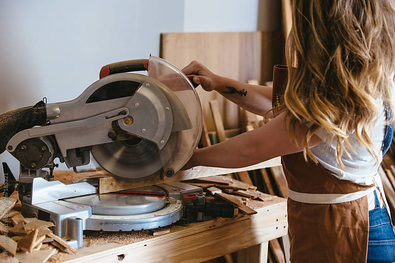 Wood making artist using a chop saw in her studio by Trinette Reed for Stocksy United
