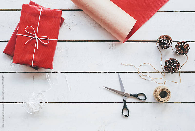 Preparing christmas presents wrapped in red paper on a wooden background by Aleksandar Novoselski for Stocksy United